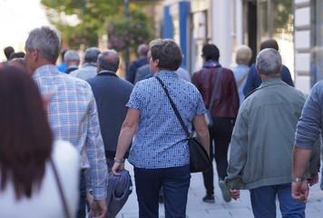 Gruppe von Touristen flaniert durch eine Geschäftsstraße