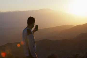 Young man looking out over a sunset from mountain viewpoint