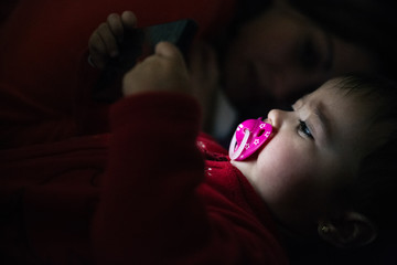 Baby using a mobile phone lying down on a bed and her mother on the background