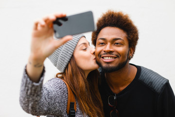 Portrait of young multi ethnic couple making a selfie with phone on white background.