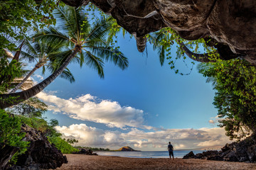 Man standing just outside of the lush Centipede Cave on the Island of Maui, Hawaii