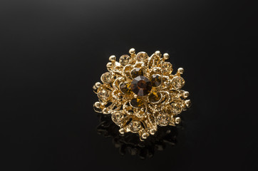 Wall Mural - gold round brooch with diamonds isolated on black