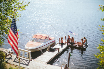 A group of friends are hanging on the dock during a summer afternoon