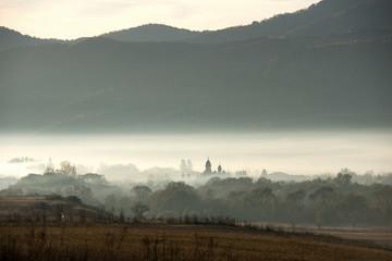 Village church in misty morning lights Wall mural