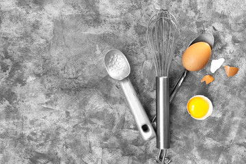 Accessories for baking a whisk, rolling pin, spoon and eggs, a concept of homemade hand-made cooking on a light marble background with a copy-space view from above