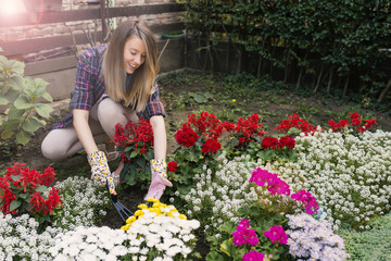 Smiling blond woman gardening. Young woman gardening outside and holding flowers