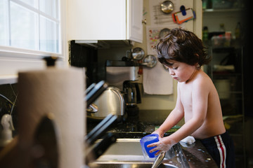 little boy playing with a cup and soapy water in a kitchen sink