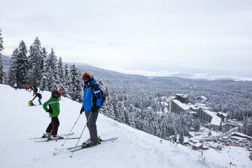 Alpine ski resort Borovets, Rila mountain, Bulgaria. Ski slope, people skiing down the hill, mountains view