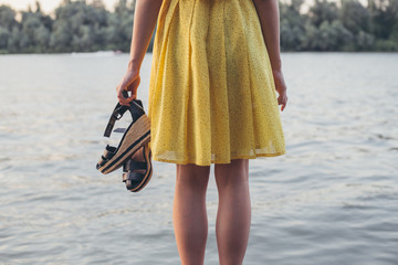 Young woman standing by a lake holding her shoes