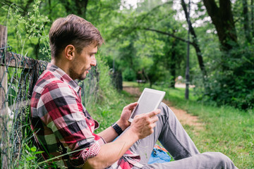 Young man sitting and reading on his tablet at the park