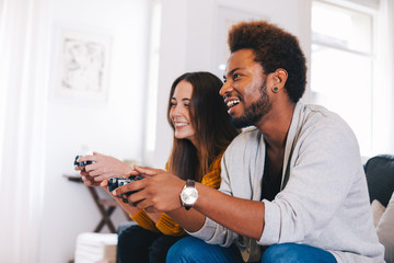 Two young friends playing video games at home.