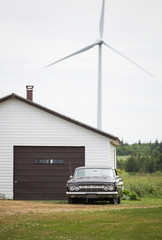 Vintage antique car near garage door with windmill outdoors