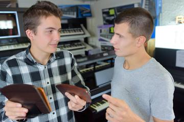 Young man choosing wood finish for keyboard