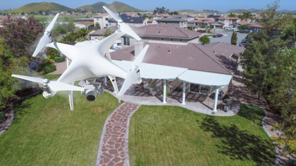 Unmanned Aircraft System (UAV) Quadcopter Drone In The Air Over House.