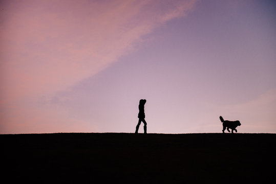 silhouette of a woman and happy dog walking outside on a cold morning