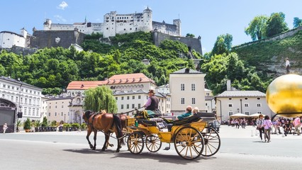 Tourists sightseeing in horse carriage in Salzburg, Austria Wall mural