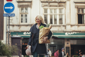 Smiling Woman Carrying a Bag With Groceries