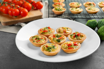 Plate with broccoli quiche tartlets on table