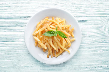 Plate with yummy french fries on wooden table