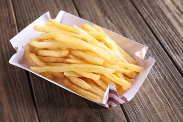 Paper container with yummy french fries on wooden table