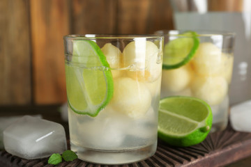 Glass of delicious cocktail with melon balls on wooden board, close up