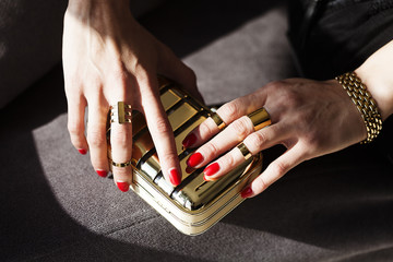 Elegant Woman's Hands on Golden Purse