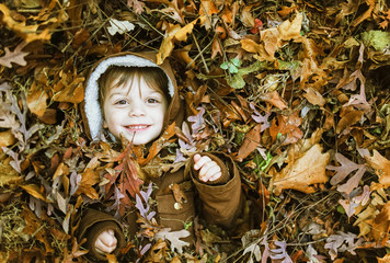 Young boy playing in the leaves after raking