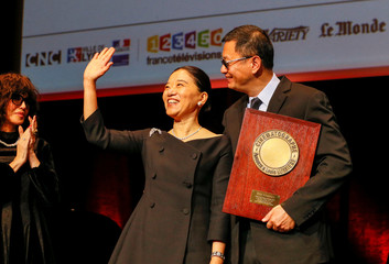 Director Wong Kar-wai, flanked by his wife Esther receives his Lumiere Award from French actor Isabelle Adjani during a ceremony at the Lumiere 2017 Grand Lyon Film Festival in Lyon