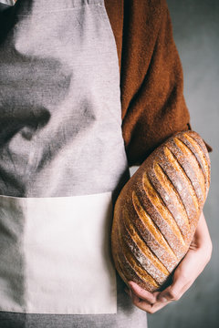 Midsection of woman wearing apron holding loaf of bread