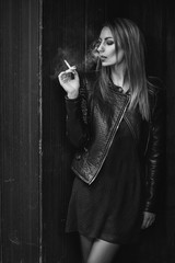 Young beautiful woman smoking a cigarette on the street