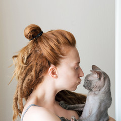 Ginger woman with dreadlocks is holding grey sphynx