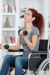 woman sitting in wheelchair working out with dumbbells