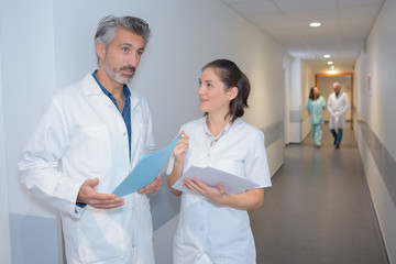 male doctor and female nurse in hospital corridor