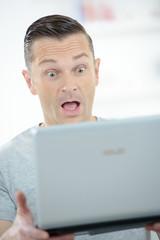 surprised man looking at computer screen
