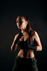 Athletic girl in sport top on black studio background. A young woman is boxing in bandages for boxing.
