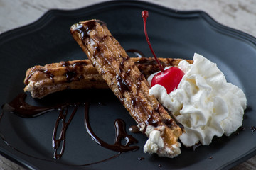 mexican churros with chocolate whipped cream and cherry