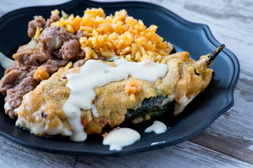 mexican chili relleno with rice and refried beans