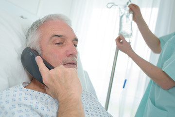 senior patient in hospital using phone