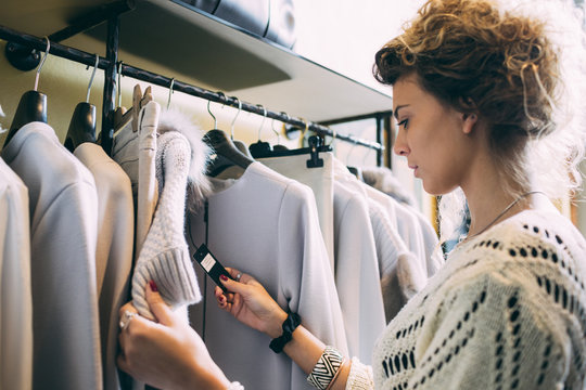 Young woman in a clothes store checking the price on the label