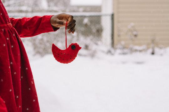African American girl holding a handmade felt bird Christmas decoration in the snow