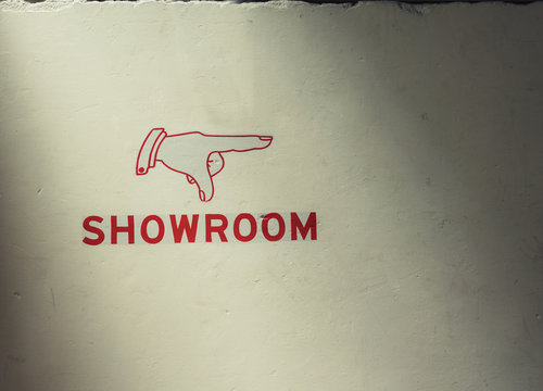 """sign on wall reading """"showroom"""" with pointing finger as an arrow"""