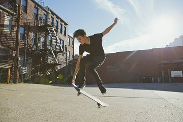 Backlit skateboarder doing a trick in a city lot