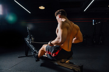 Fitness young man using rowing machine in the gym