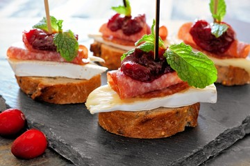 Foto op Plexiglas Voorgerecht Holiday crostini appetizers with cranberry sauce, brie, salami, and mint close up on a slate server