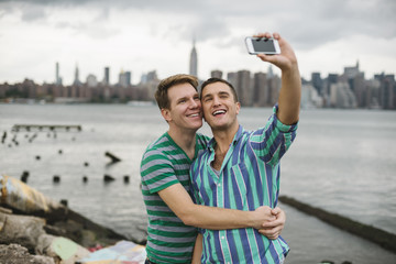Gay couple taking a selfie against Manhattan skyline