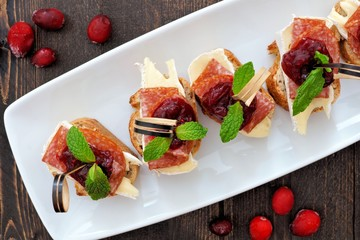 Spoed Fotobehang Voorgerecht Holiday crostini appetizers with cranberry sauce, brie, salami, and mint above view on a white serving plate