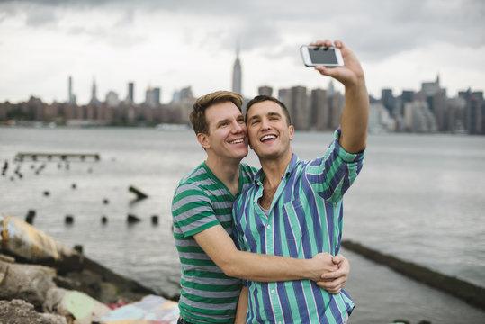 Gay couple taking a selfie against Manhattan skyline