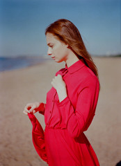 Portrait of the beautiful woman in red dress looking away