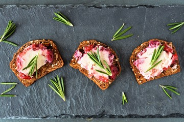Holiday cracker appetizers with cranberry cheese and rosemary, above view on a slate server