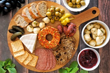 Appetizer platter with an assortment of cheeses, crackers, meats and snacks above scene with a wood background